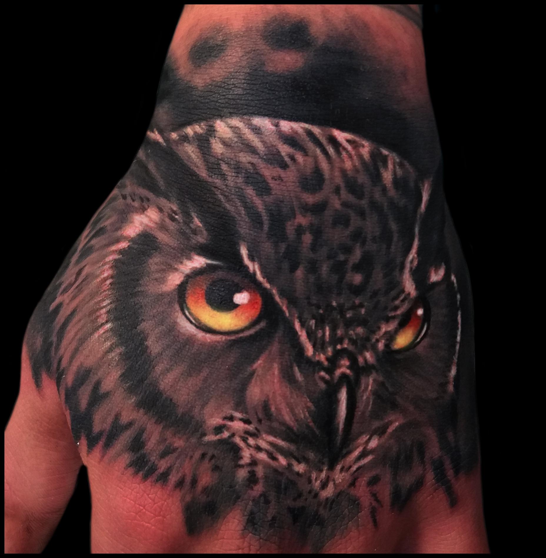 mano tatuada con búho